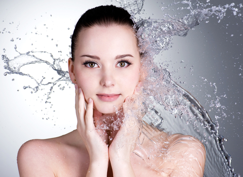 splashes of water on the beautiful face of young woman-img-blog