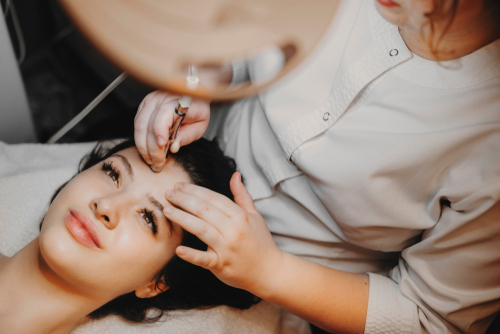 upper view lovely female face leaning on a spa bed with eyes opened doing noninvasive microdermabrasion on her face-img-blog