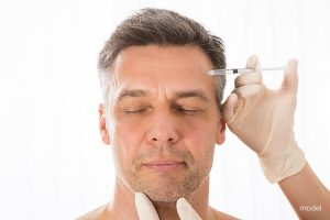 Man with eyes closed and needle to forehead.