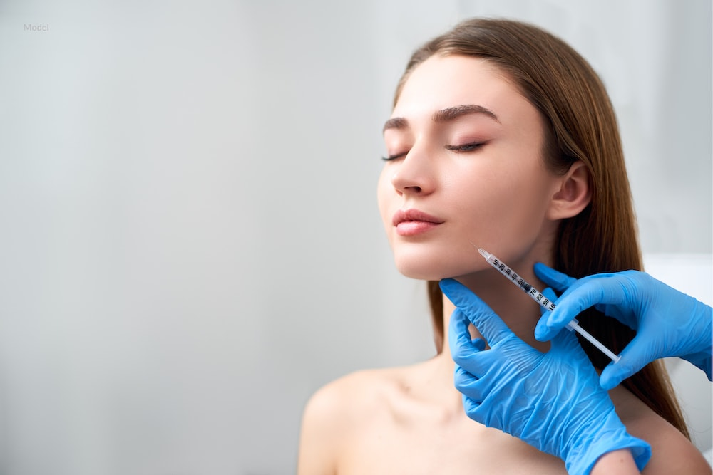 Women receiving a dermal filler injection in her jawline.