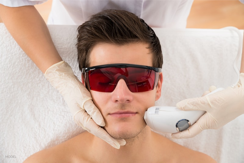 Beautician Giving Laser Treatment To Young Man Face