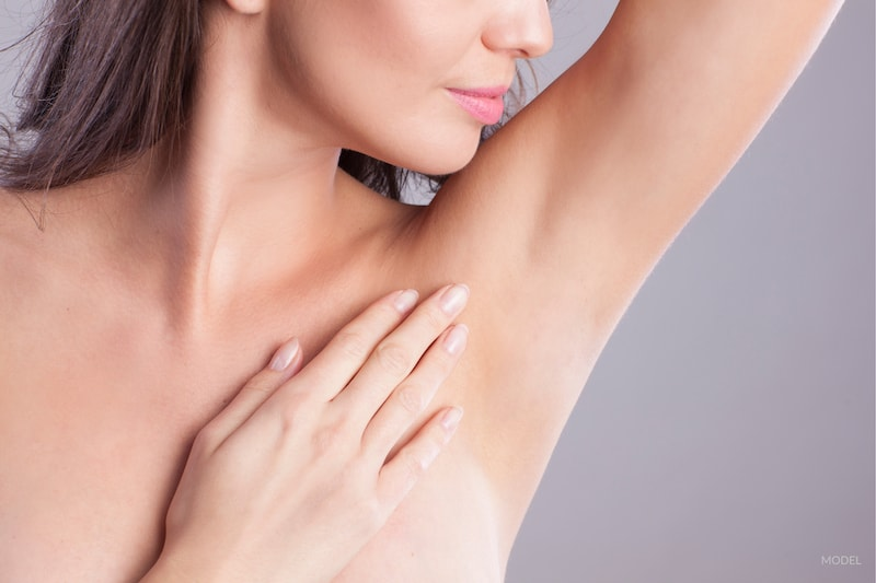 Woman touching her smooth, hair-free armpit. Results possible with laser hair removal.